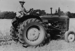 The reluctant cowboy: me on the farm — after I was promoted from shovelling manure to driving a tractor.