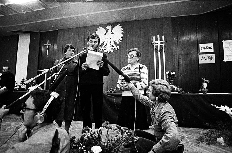 Andrzej Kołodziej at the mic; Anna Walentynowicz stands to his left.  Lenin Shipyard in Gdańsk; Aug. 20, 1980