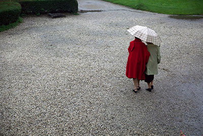 Childhood friends walk arm-in-arm under the rain in Poland during the reunion.