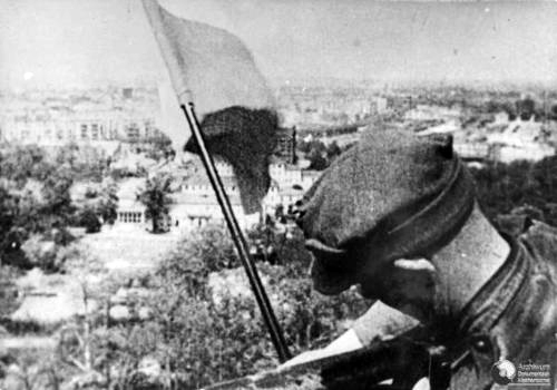 May 1945: Polish soldier Mikołaj Troicki arranges the Polish flag in Berlin.
