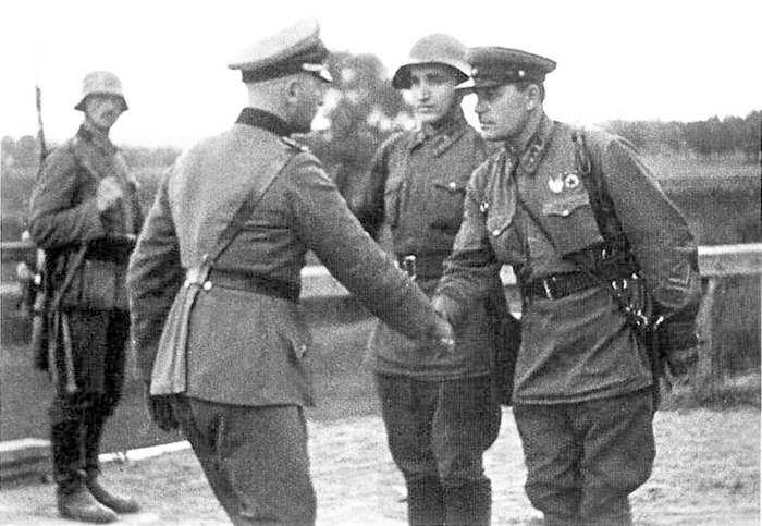 "PHOTO published in October 1939 via TASS (Telegraphic Agency of the Soviet Union), The caption reads, ""German and Soviet officers shake hands at the end of the invasion of Poland."" The date of the photo is September 1939."